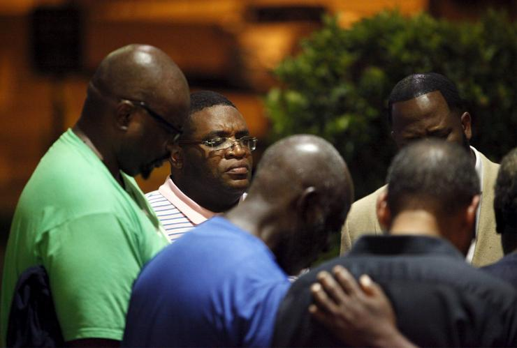 A small prayer circle forms nearby where police are responding to a shooting at the Emanuel AME Church in Charleston, South Carolina June 17, 2015. Reuters/Randall Hill